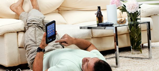 man relaxing in the living room, with tablet-pc, feet up