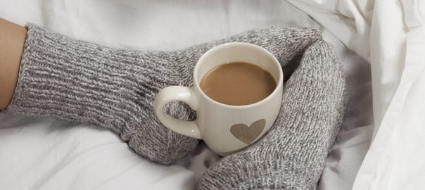A cup of coffee or hot chocolate and female feet with socks on a white sheets.