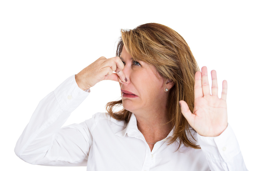 Closeup portrait, mature beautiful, unhappy woman who covers her nose, looks at you, something stinks, very bad smell, situation, isolated white background. Human facial expressions, emotions